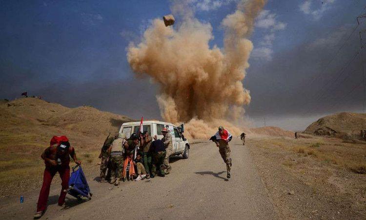 عناصر من الحشد الشعبي يركضون أثناء سقوط قذيفة في ضواحي الحويجة، العراق، 30 سبتمبر 2017 (REUTERS )